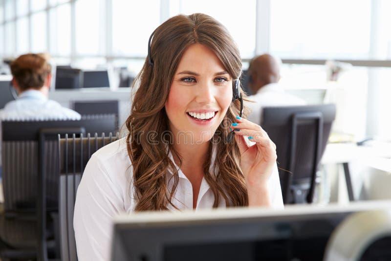 Молодая женщина работая в центре телефонного обслуживания, держа шлемофон стоковое фото