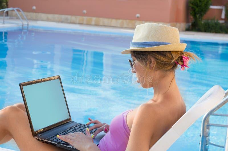 Молодая женщина работая на его компьтер-книжке бассейном пока на каникулах стоковые фото