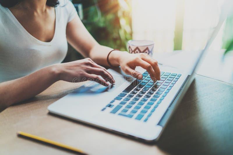 Молодая женщина работая дома на современном компьютере Девушка печатая на клавиатуре компьтер-книжки пока сидящ на деревянном сто стоковое фото rf