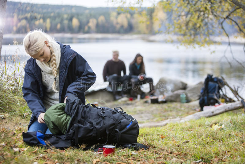 Молодая женщина распаковывая рюкзак на месте для лагеря стоковое фото rf