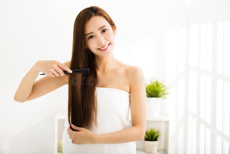 Молодая женщина расчесывая ее волосы в живущей комнате стоковое фото