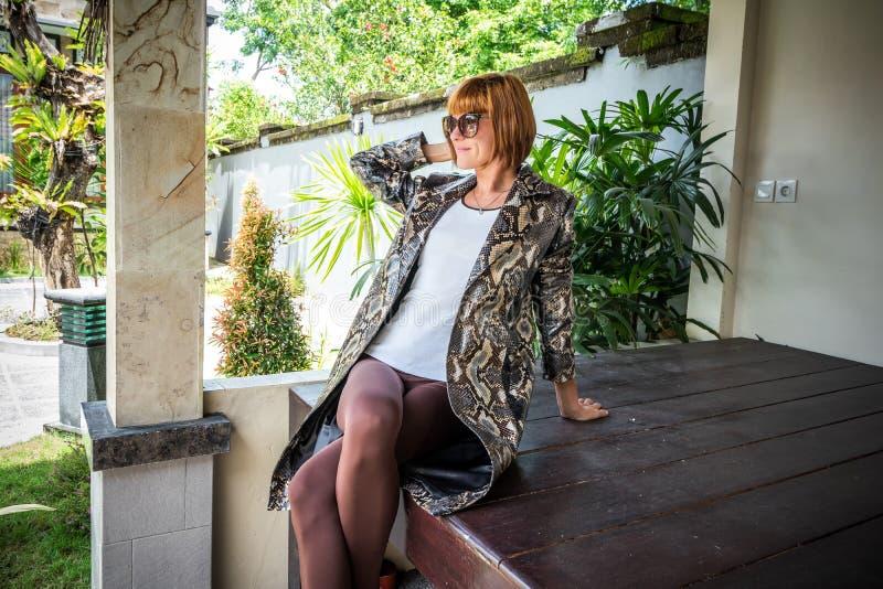 Молодая женщина, роскошный плащ накидки питона snakeskin моды Handmade пальто snakeskin стоковые изображения rf