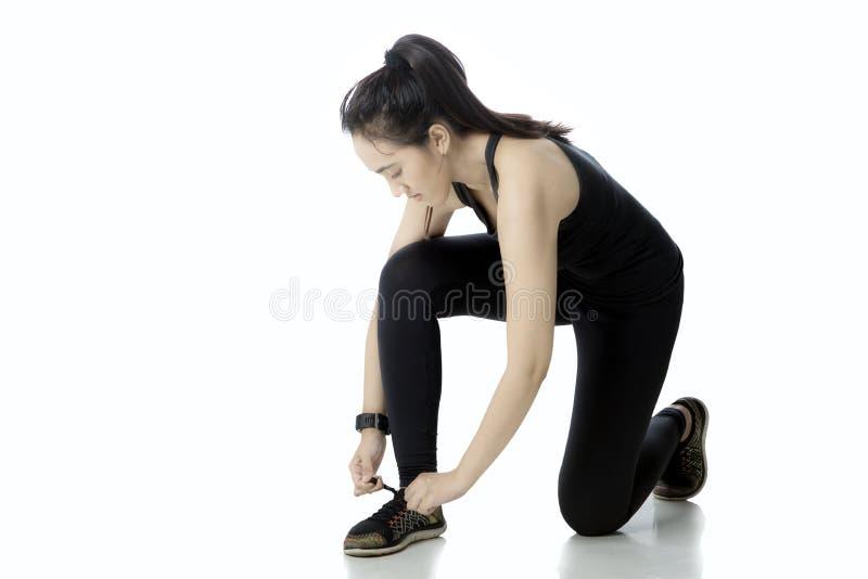 Молодая женщина связывая ее шнурки стоковое фото rf