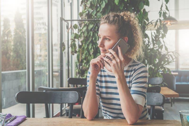 Молодая женщина сидит в кафе на деревянном столе и говорит на мобильном телефоне Девушка ждет друзей стоковая фотография rf