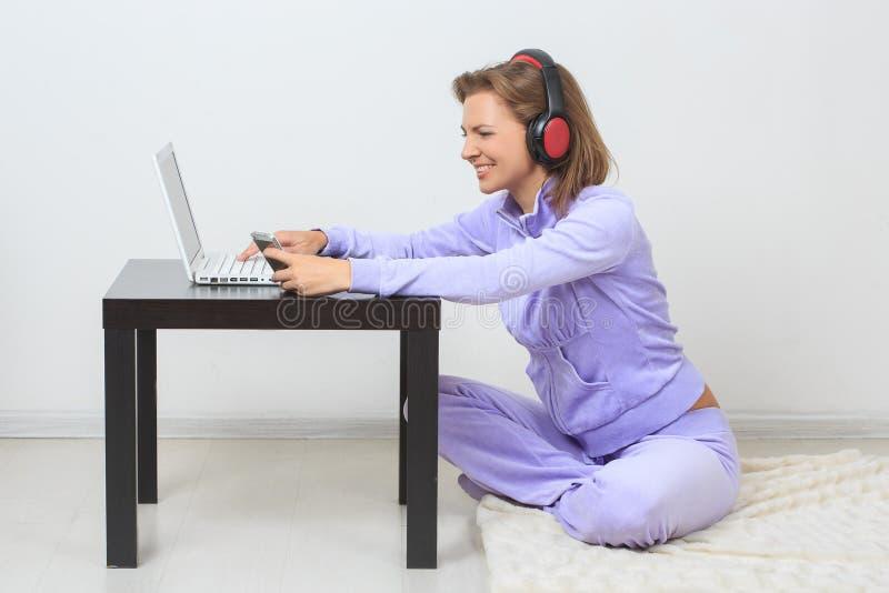 Молодая женщина сидит на поле, слушая музыке стоковые фотографии rf