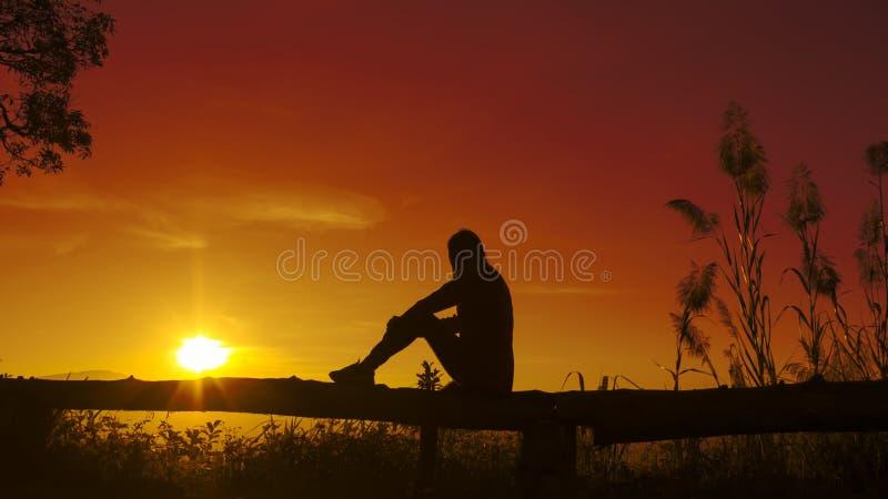 Молодая женщина силуэта захода солнца унылая стоковое изображение rf