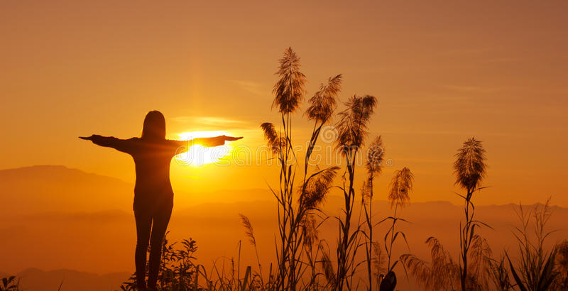 Молодая женщина силуэта захода солнца чувствуя к свободе и ослабляет стоковая фотография rf