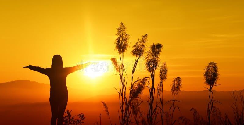 Молодая женщина силуэта захода солнца чувствуя к свободе и ослабляет стоковое фото