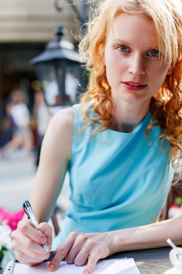 Молодая женщина сидя в документах кафа и знака стоковая фотография rf