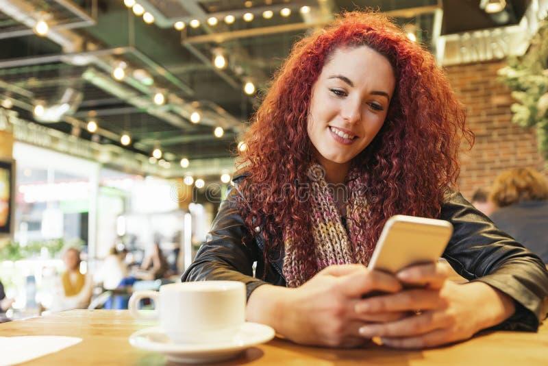 Молодая женщина сидя в ультрамодном сочинительстве кафа с ее мобильным телефоном стоковые изображения rf