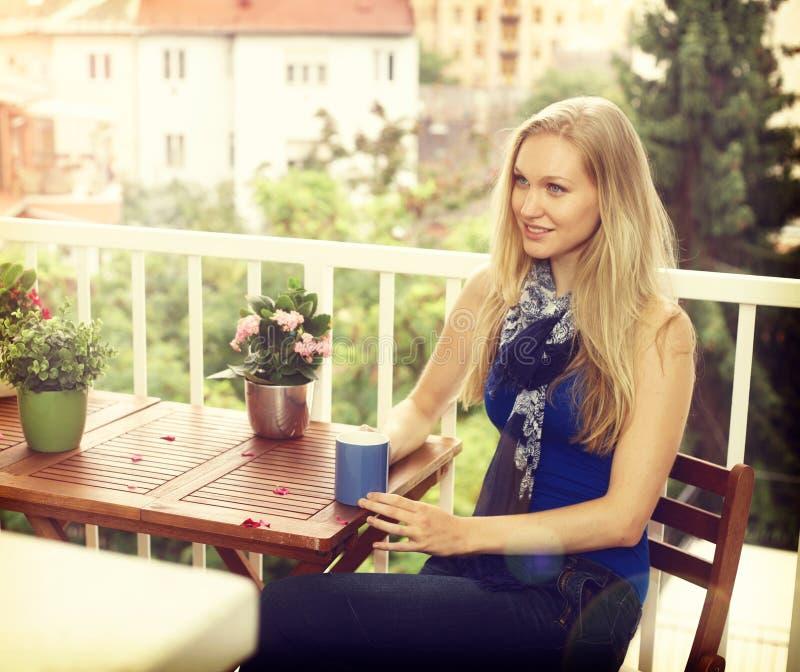 Молодая женщина сидя на балконе стоковая фотография rf