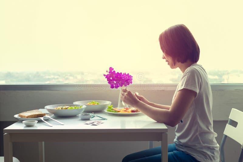 Download Молодая женщина сидя на комнате на таблице и есть обедающий самостоятельно Стоковое Изображение - изображение насчитывающей довольно, портрет: 81812671