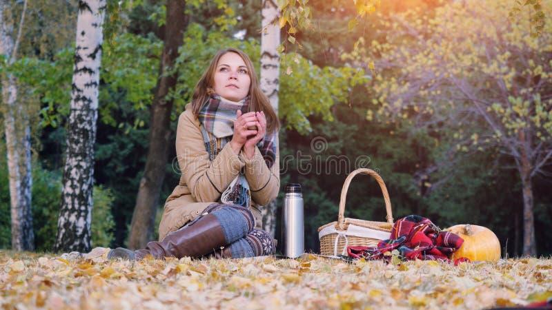 Молодая женщина сидя на пикнике выпивая горячий чай от thermos в парке осени Девушка половик около тыквы хеллоуина стоковая фотография rf