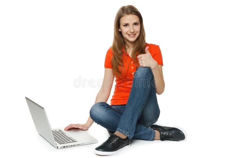 Женщина сидя на поле при ее компьтер-книжка делая большой палец руки вверх стоковые фотографии rf