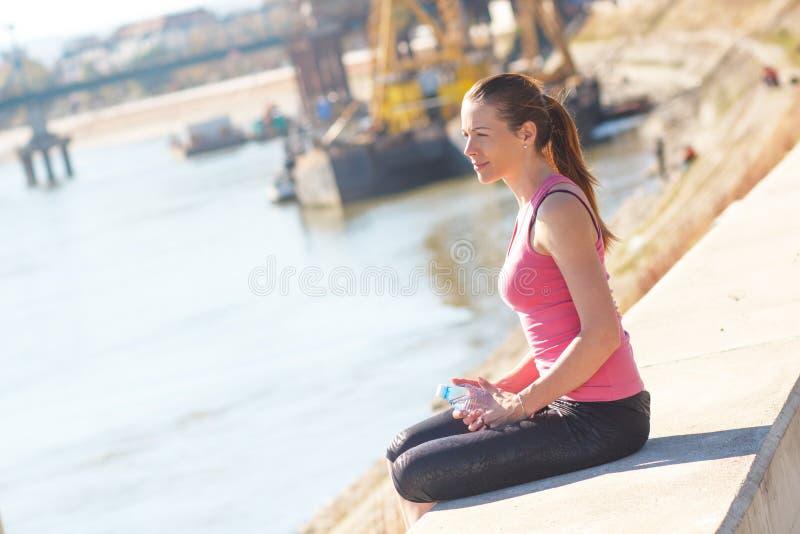 Молодая женщина сидя на речном береге и отдыхая после jogging стоковые фотографии rf