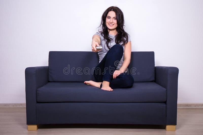 Молодая женщина сидя на софе и смотря ТВ дома стоковые изображения