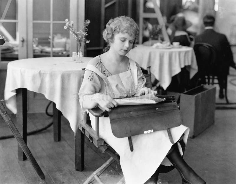 Молодая женщина сидя на стуле и читая документы (все показанные люди более длинные живущие и никакое имущество не существует Пост стоковое изображение