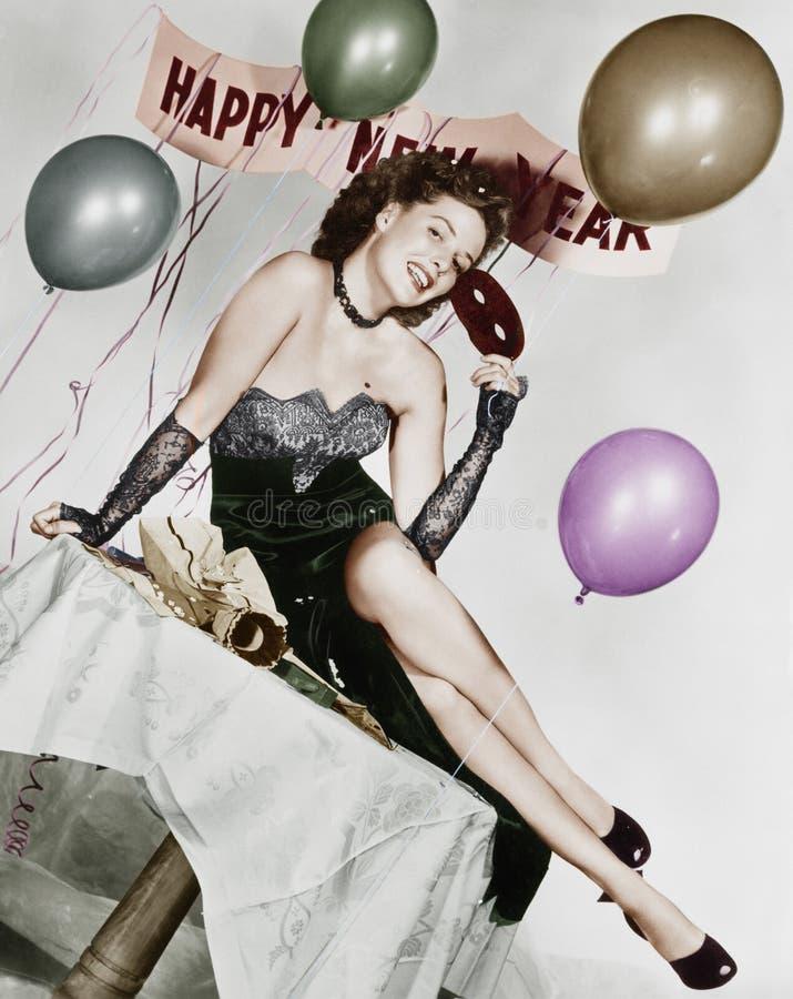 Молодая женщина сидя на таблице с воздушными шарами и знак (все показанные люди более длинные живущие и никакое имущество не суще стоковые фото