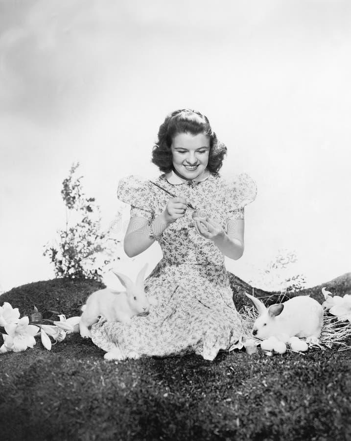 Молодая женщина сидя на траве при кролики крася пасхальное яйцо (все показанные люди нет более длинные живущих и никакого имущест стоковое фото rf
