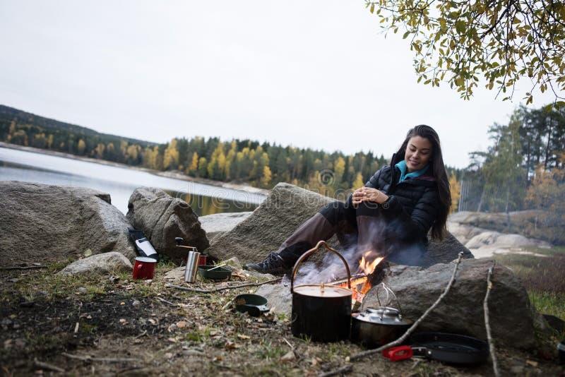 Молодая женщина сидя около лагерного костера дальше Lakeshore стоковые фото