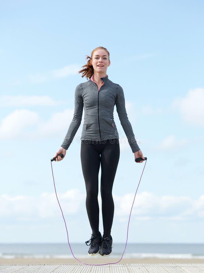 Молодая женщина скача с прыгая веревочкой outdoors стоковая фотография rf