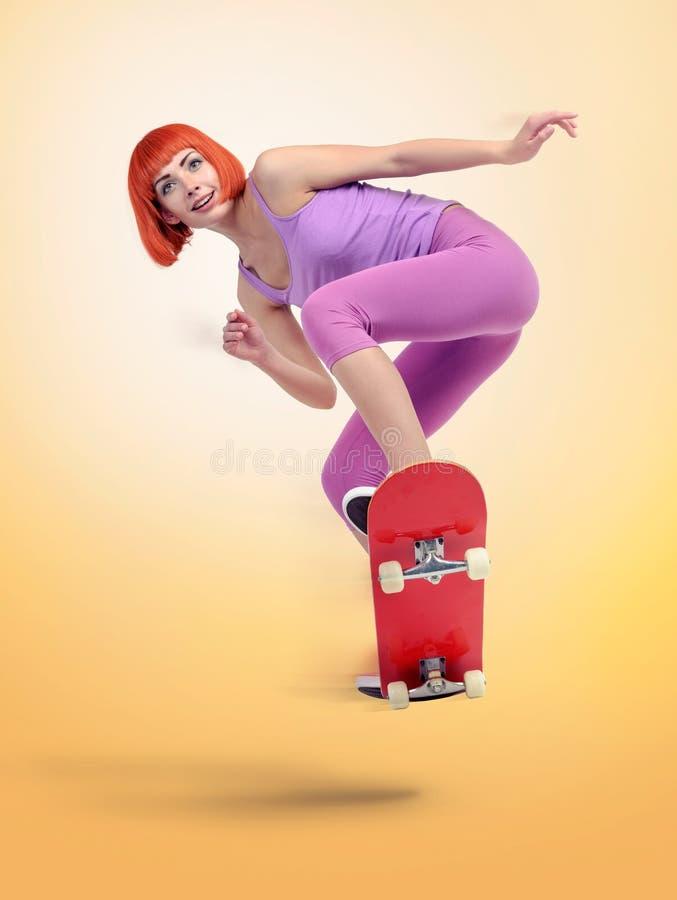 Молодая женщина скейтбордиста скача на желтую предпосылку стоковое изображение rf