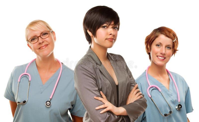 Молодая женщина смешанной гонки с докторами и медсестрами позади стоковая фотография