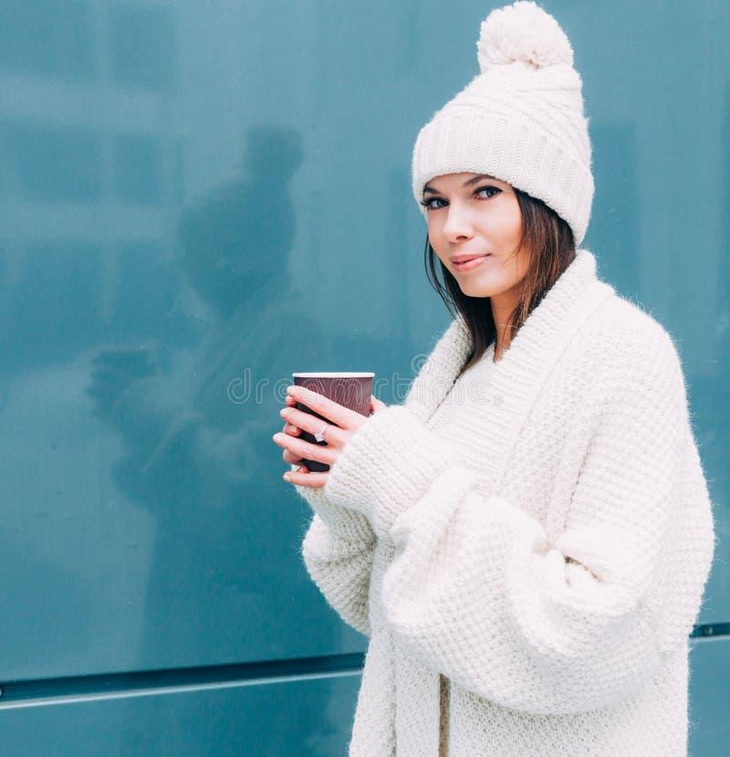 Молодая женщина смотрителя битника выпивает кофе на улице пока идущ на холодный зимний день Модельное нося белое пальто стоковая фотография
