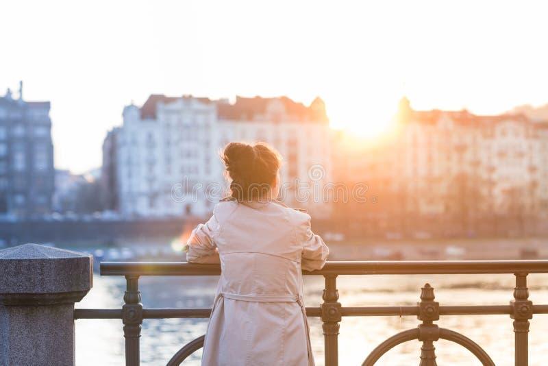 Молодая женщина смотрит заход солнца стоковое изображение rf