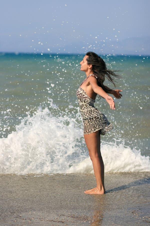 Молодая женщина смотря на волны стоковые фото