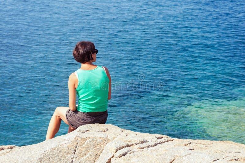 Молодая женщина смотря на море стоковые изображения