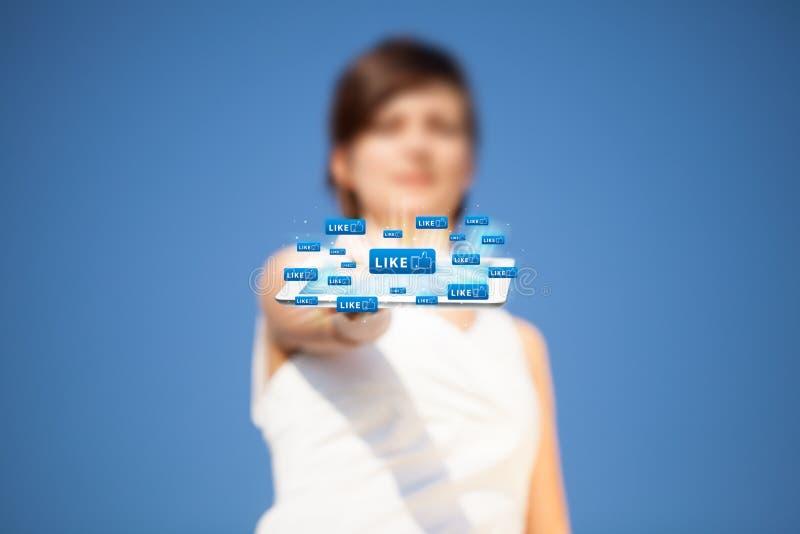 Молодая женщина смотря современную таблетку с абстрактными светами и так стоковая фотография