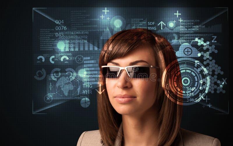 Молодая женщина смотря с футуристическими умными высокотехнологичными стеклами стоковое фото rf