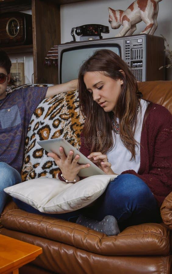 Молодая женщина смотря электронную таблетку сидя дальше стоковое фото rf