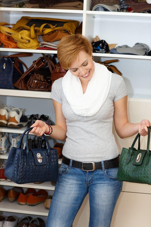 Молодая женщина смущаясь среди сумок стоковое фото