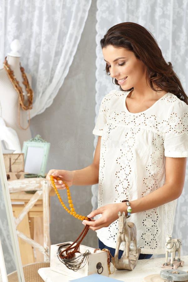 Молодая женщина сортируя аксессуары стоковое фото rf