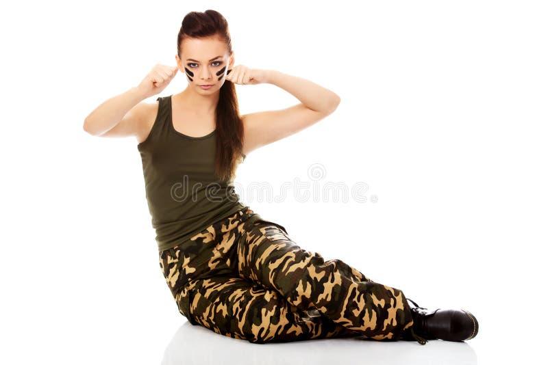 Молодая женщина солдата сидя на поле и класть в коробку стоковая фотография rf