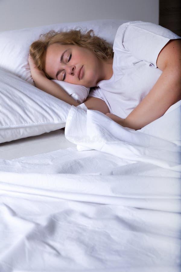 Молодая женщина спать в кровати на ноче стоковое фото