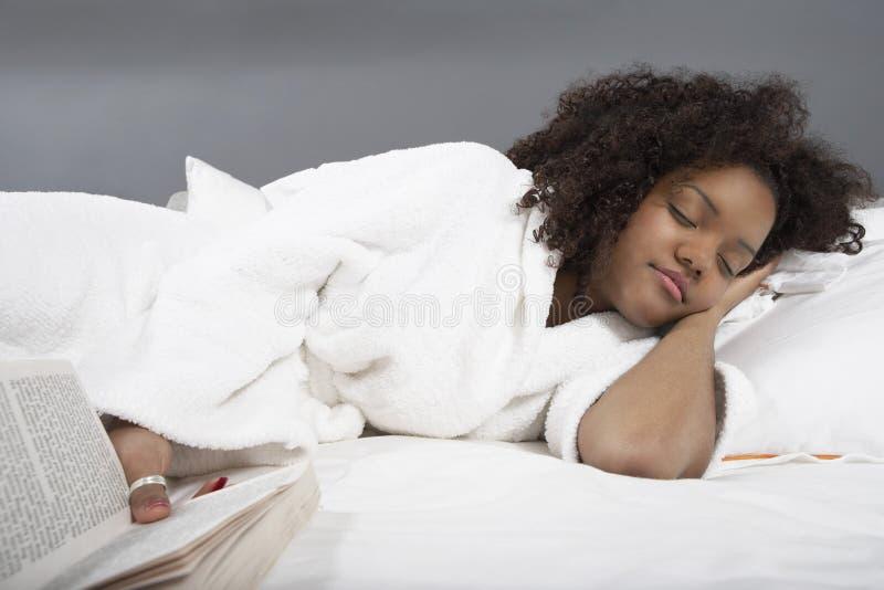 Молодая женщина спать в кровати стоковые фотографии rf