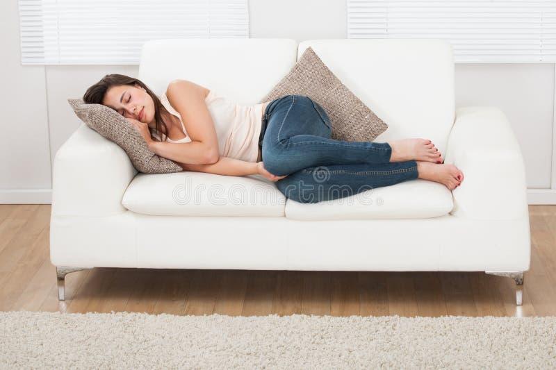 Молодая женщина спать на софе дома стоковая фотография rf