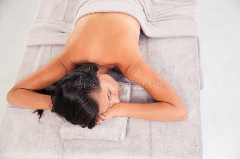 Молодая женщина спать на lounger массажа стоковое фото rf