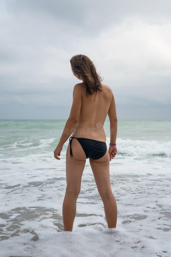 Молодая женщина стоя в волнах стоковое изображение rf