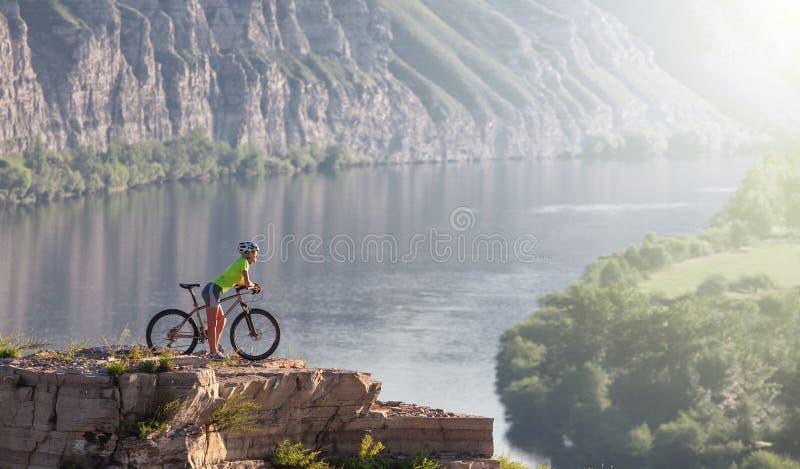 Молодая женщина стоя в горе с велосипедом над рекой стоковые фото