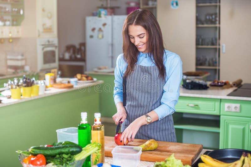 Молодая женщина стоя в ее варить рисбермы кухни нося, режа плодоовощ на доске стоковое изображение rf