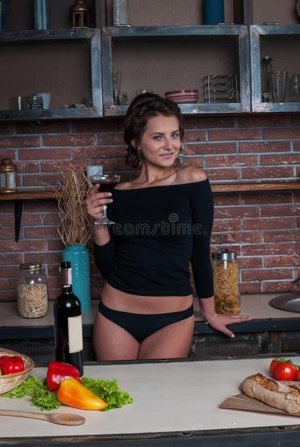 Молодая женщина стоя в кухне держа красный бокал стоковое фото rf