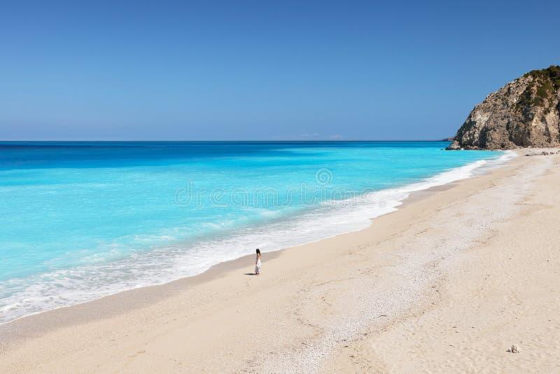 Молодая женщина стоя на пляже стоковые изображения