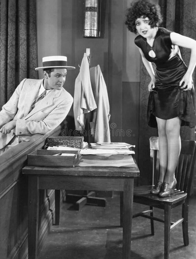 Молодая женщина стоя на стуле при молодой человек смотря ее ноги (все показанные люди нет более длинные живущих и никакого имущес стоковые изображения rf