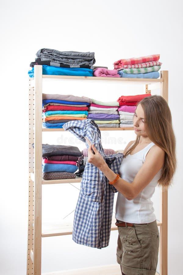 Молодая женщина стоя около шкафа стоковая фотография