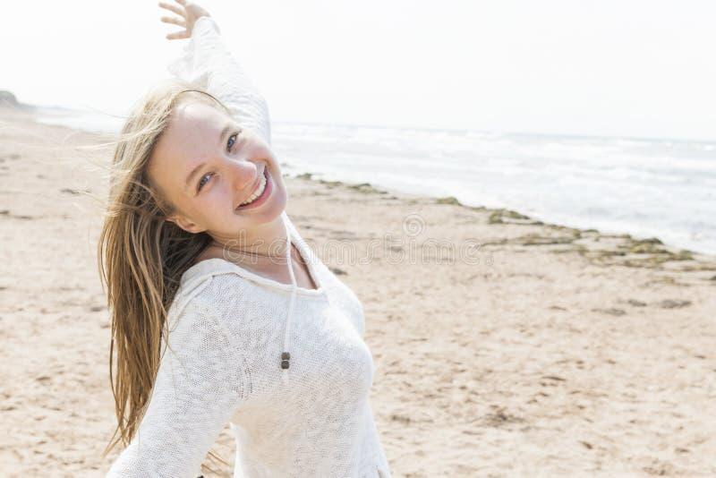Молодая женщина счастливая на пляже стоковое фото