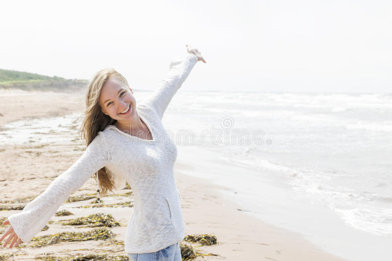 Молодая женщина счастливая на пляже стоковое изображение